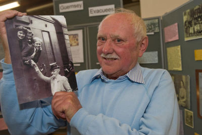 John Helyer (evacuee) with photo of himself taken in 1945 on a trip from Bury to Guernsey to see his family