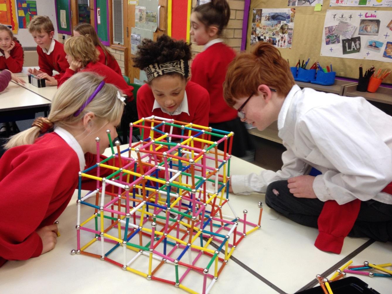 Three school children gathered around a plastic structure