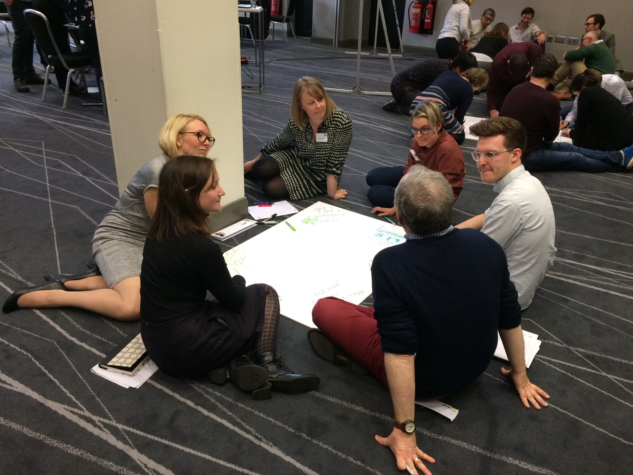 Image of people sitting in a circle brainstorming
