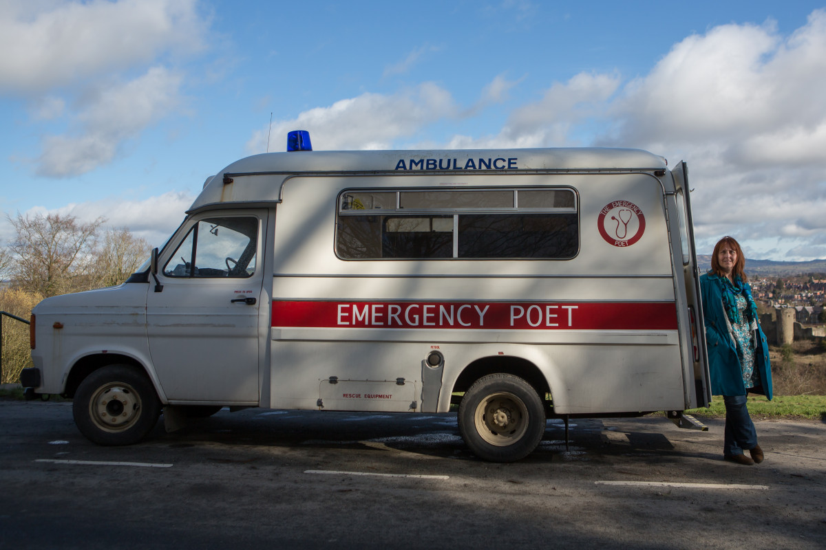 A photograph of a white van parked on a road in front of blue skies. A woman in a blue coat is leaning on the van and looking at the photographer. The van has been decorated to look like an ambulance. It says 'AMBULANCE' at the top and 'EMERGENCY POET' lower down.