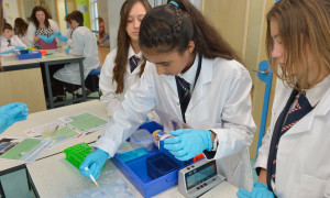 Three school children in lab coats conducting a science experiment