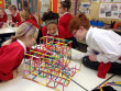 Three school children gathered around a plastic structure