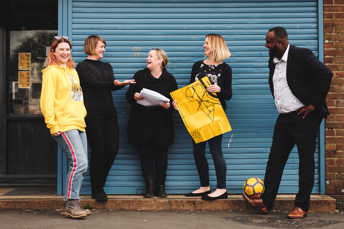A photograph of five people standing in front of a wall, looking at each other and smiling and laughing. Two of them are hold pieces of paper and one has a football at his feet.